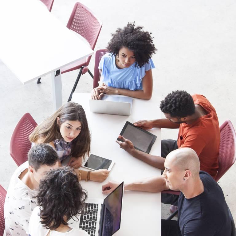 5 studenten aan tafel aan het werk