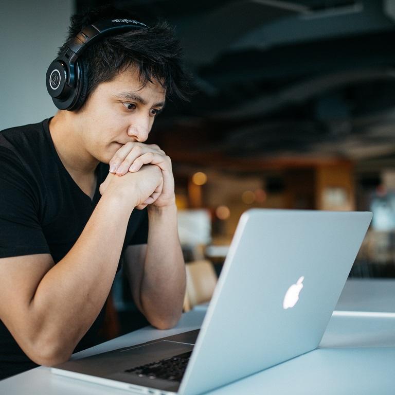 man met koptelefoon achter laptop