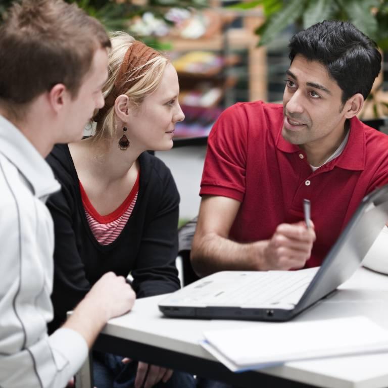 die personen overleggen aan een tafel met laptop