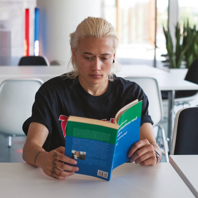 jongen aan tafel leest een folder
