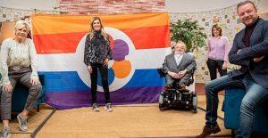 vier personen staan voor vlag voor mensen met een beperking