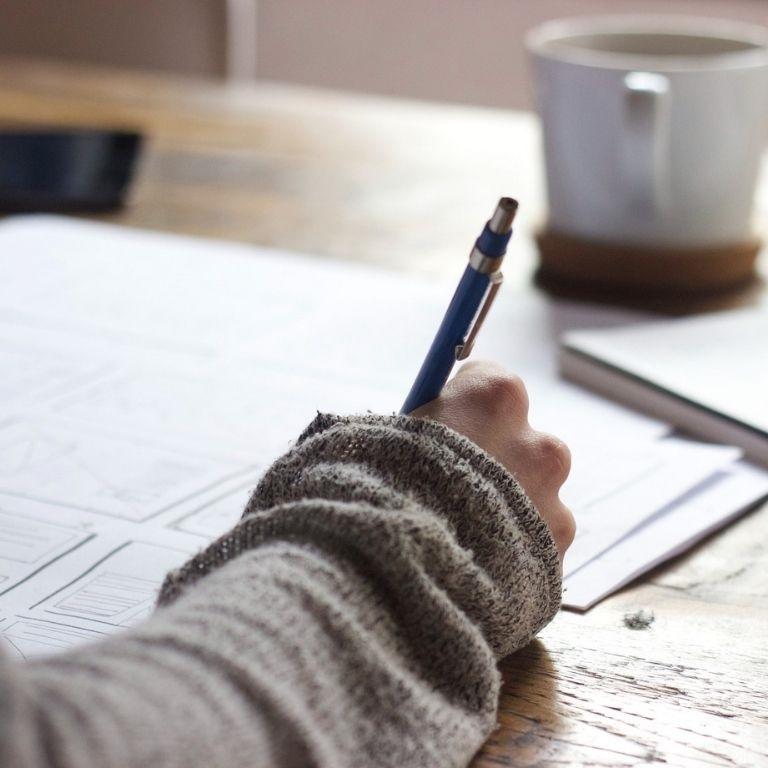 Arm met pen in de hand ligt op tafel met kop koffie