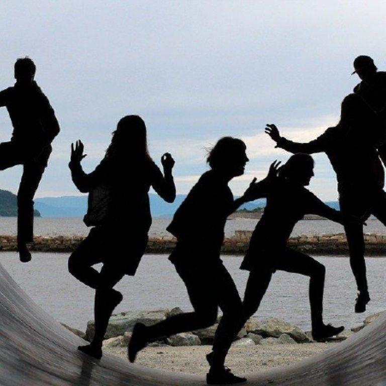 5 mensen in schaduw lopen op een skatebaan
