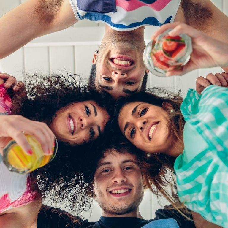 4 studenten in een kring met de hoofden tegen elkaar