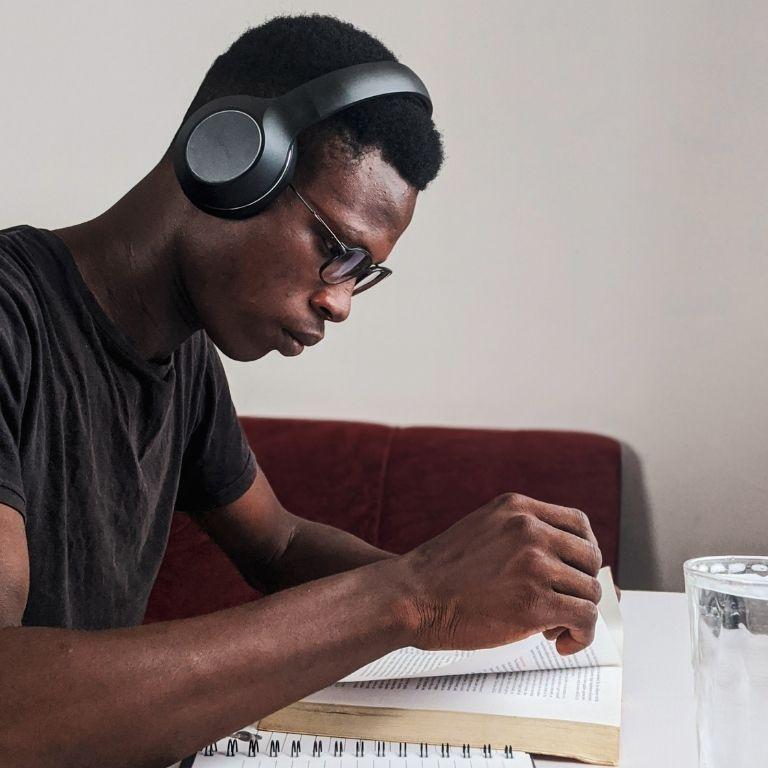 Internationale student met koptelefoon leest in een boek