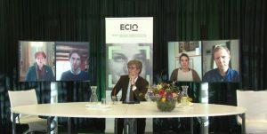 een persoon aan tafel, vier personen op afzonderlijke beeldschermen erachter en banner met ECIO