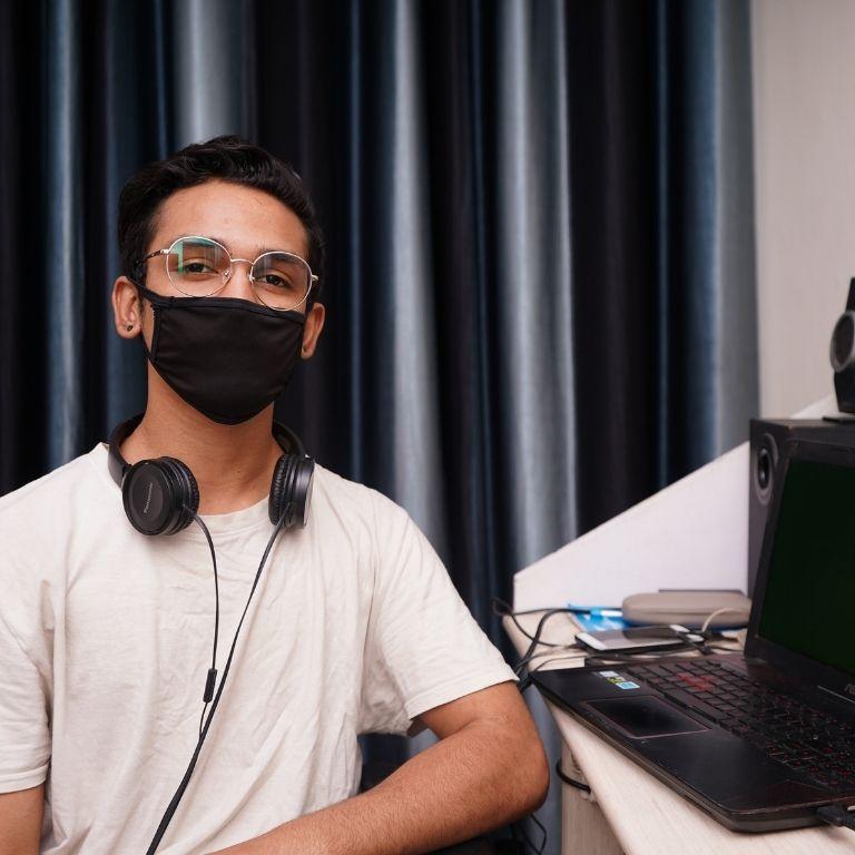 student met zwart mondkapje en headset om de net