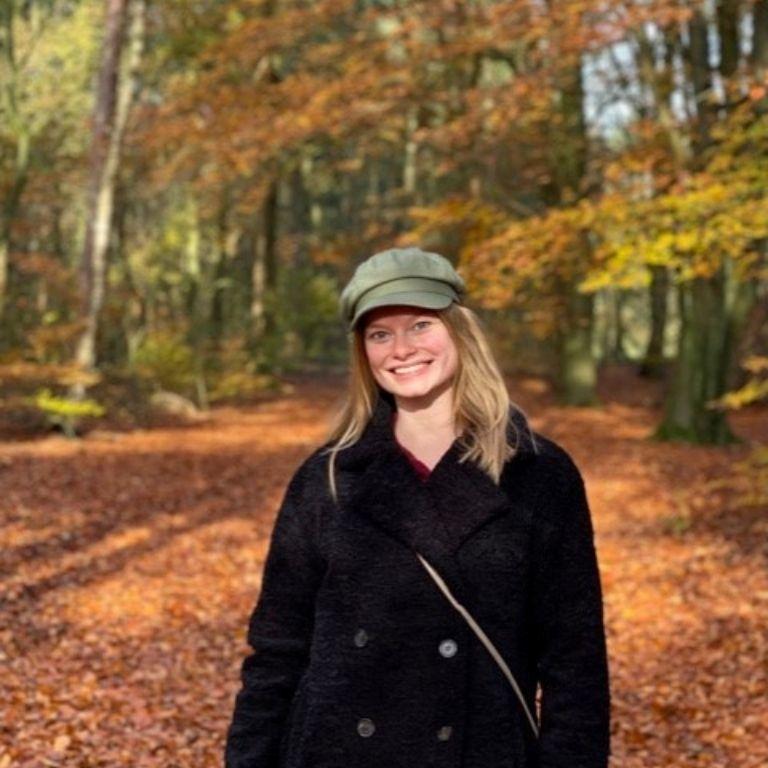 meisje met groene pet, zwarte jas en lange haren in het bos