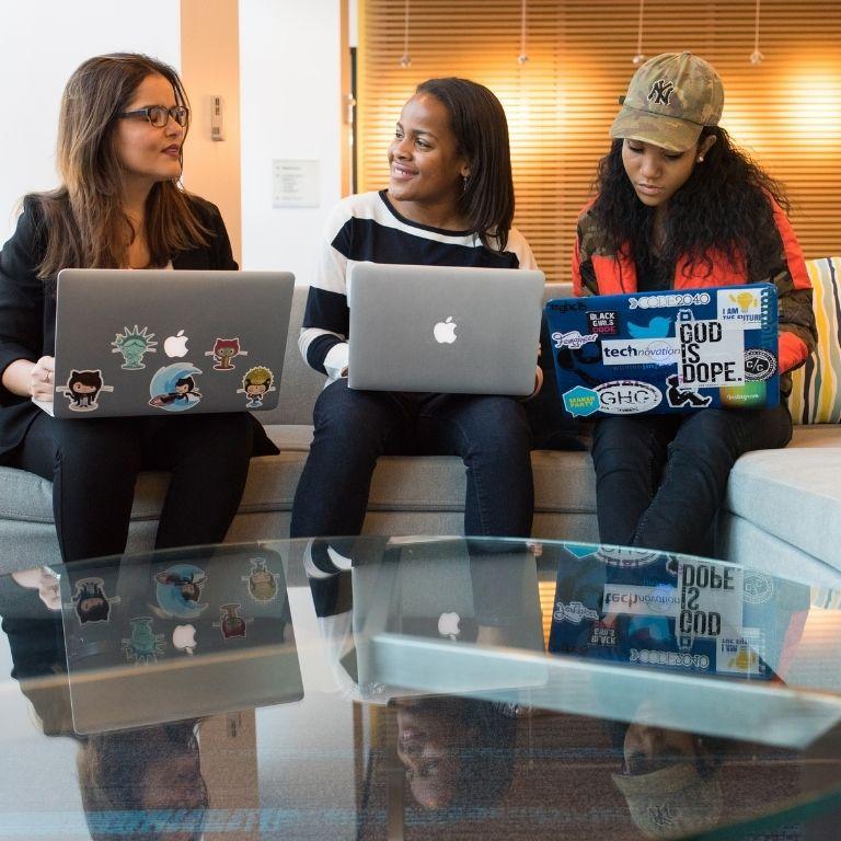 drie studenten met laptop op schoot