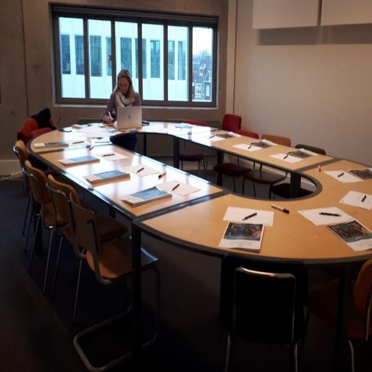 ovale tafel met brochures,notitieblokken en pennen die worden klaargelegd door een vrouw met lang blond haar