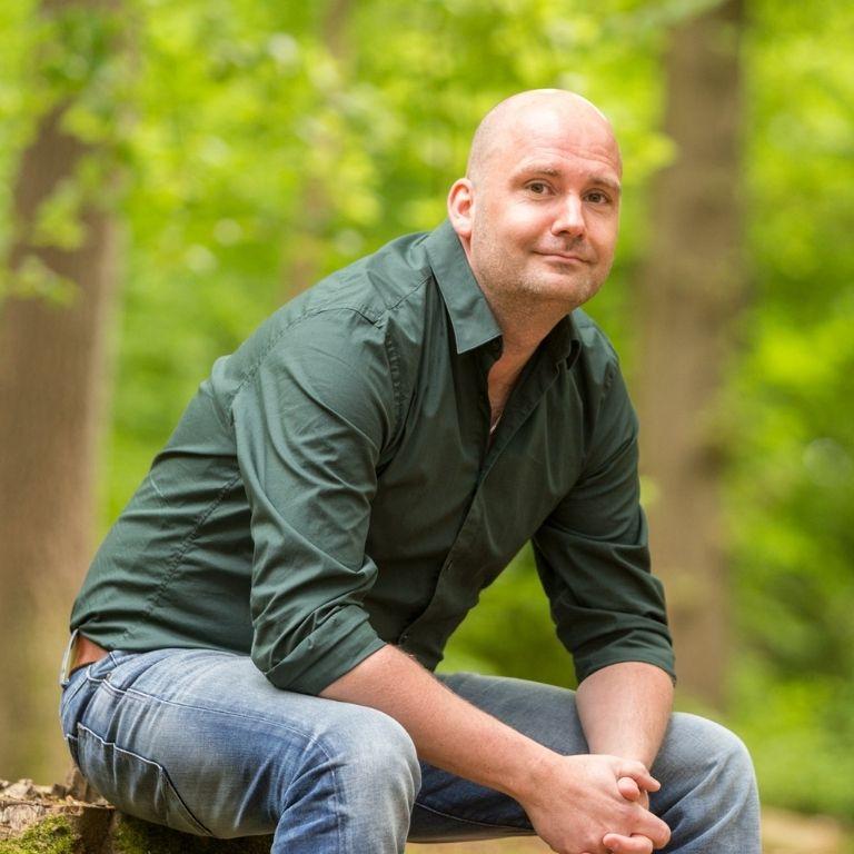 Jaap Noppers kalende man met groene blouse zittend op een boomstam